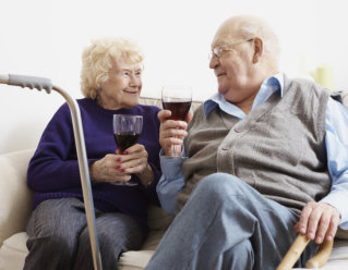 elderly couple holding a glass