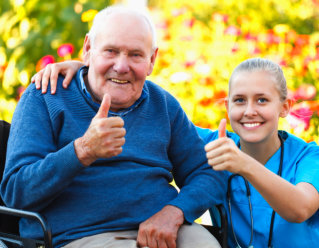 caregiver and elderly woman showing thumbs up