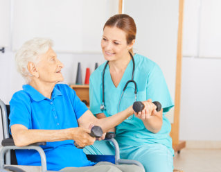caregiver assisting elderly woman in using dumbbell