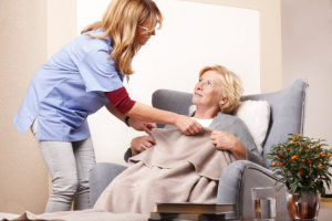 caregiver setting up the blanket for elderly woman