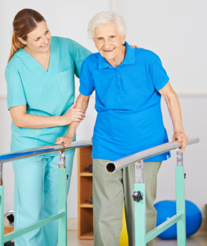 caregiver assisting elderly woman on movement exercise