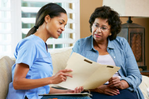 caregiver discussing records with elderly woman